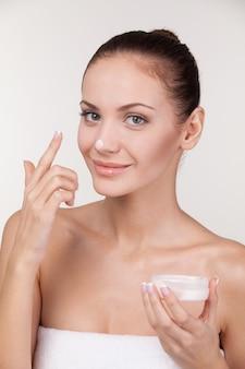Обожаю этот крем. красивая молодая женщина со сливками на носу, улыбаясь в камеру, стоя на сером фоне