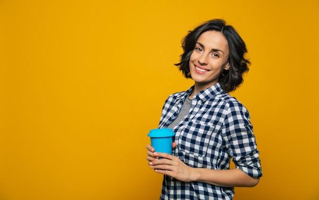 Я люблю этот день. расслабленная симпатичная девушка с яркими глазами в черно-белой клетчатой рубашке, держащая в правой руке синюю чашку, стоящая в стороне.
