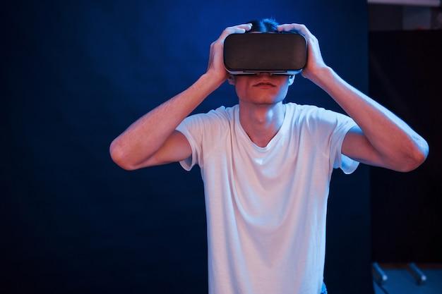 Мне это нравится. молодой человек в очках виртуальной реальности в темной комнате с неоновым освещением.