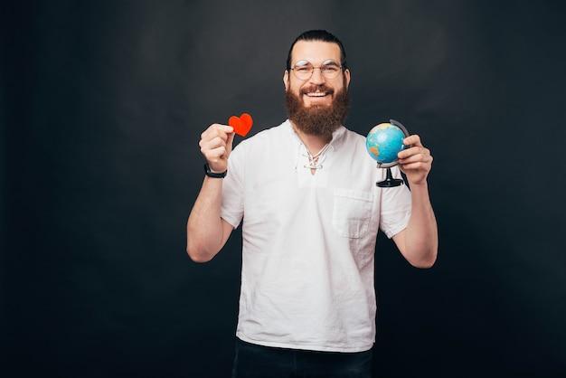 Я люблю путешествовать, веселый молодой человек с бородой держит глобус и красное бумажное сердце
