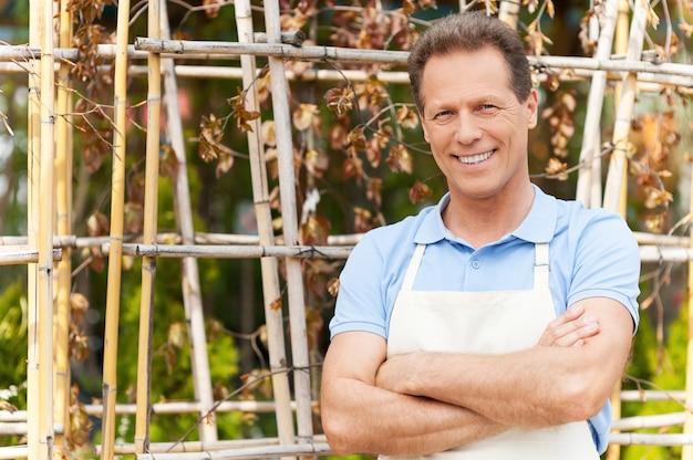 나는 식물과 함께 일하는 것을 좋아합니다. 온실에 서 있는 동안 팔짱을 끼고 웃고 있는 앞치마를 입은 잘생긴 성숙한 남자