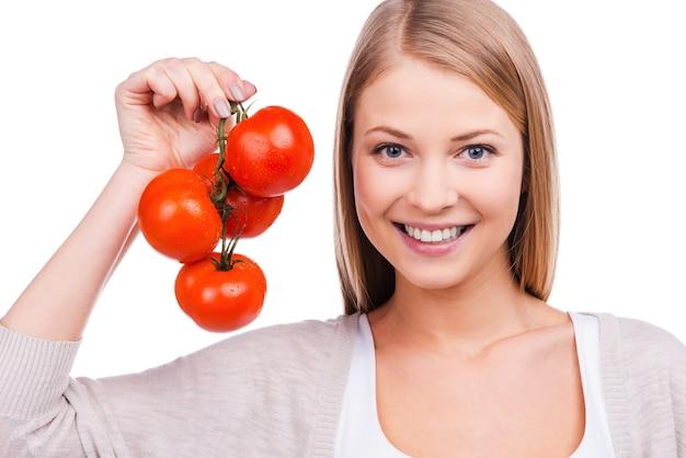 나는 토마토를 좋아한다! 토마토를 들고 흰색 배경에 서서 웃고 있는 아름다운 젊은 여성