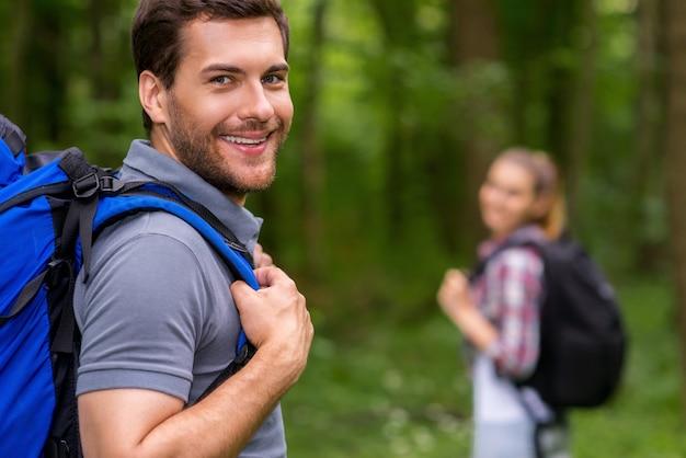 나는 여행을 좋아한다. 배낭을 메고 어깨 너머로 보고 웃고 있는 잘생긴 청년