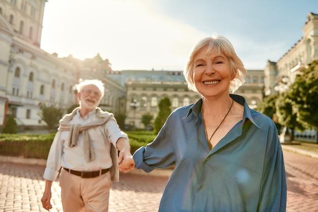 함께 시간을 보내며 손을 잡고 웃고 있는 아름답고 행복한 노부부 사랑해요