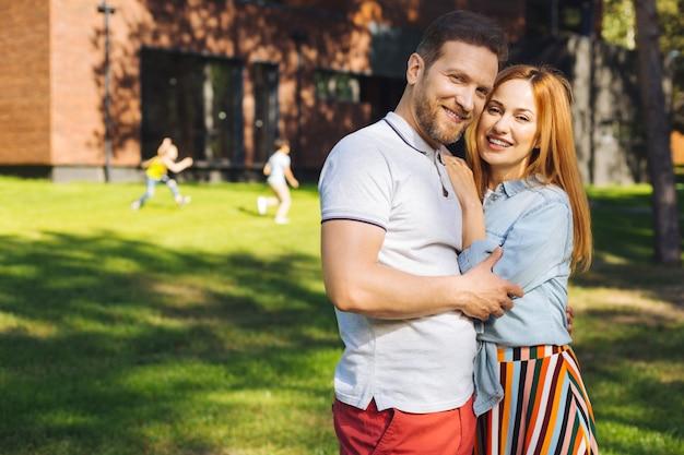 わたしは、あなたを愛しています。妻を抱きしめて笑っているコンテンツひげを生やした男