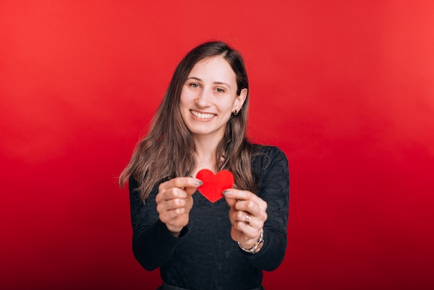 I love you. cute young girl is holding a red heart in front of her on red space.