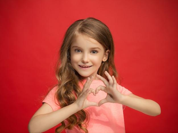 わたしは、あなたを愛しています。トレンディな赤いスタジオの背景に孤立して笑顔、立っている幸せな十代の少女。美しい女性の肖像画。若い満足の女の子