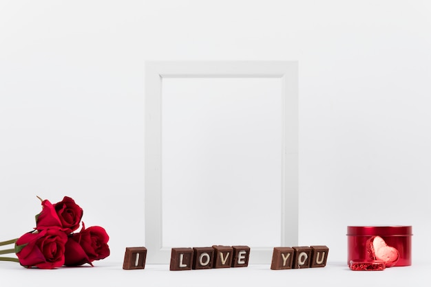 I love you inscription on chocolate pieces near photo frame, flowers and box