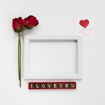 I love you inscription on chocolate pieces near photo frame, flowers and cards