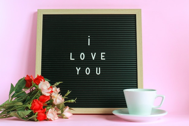 I love you on letter board with cup of coffee and roses isolated on pink background