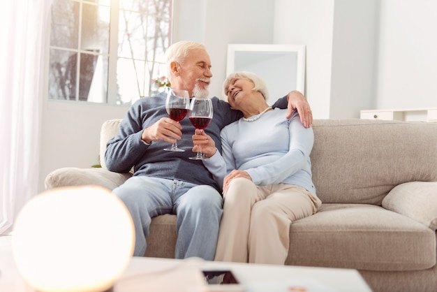 I love you. lovely elderly couple cuddling on the couch and making a toast to love while exchanging admiring looks