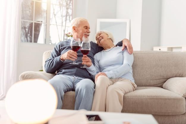 わたしは、あなたを愛しています。ソファに寄り添い、見た目を交換しながら愛する乾杯をする素敵な老夫婦