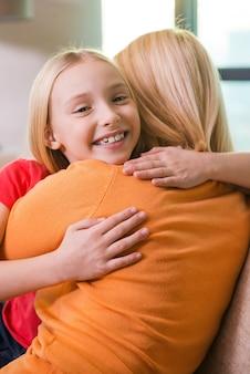 Я люблю тебя, мама! счастливая мать и дочь обнимаются, сидя на диване вместе