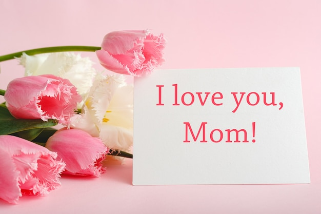 I love you mom text on gift card in flower bouquet on pink background. greeting card for mom. happy mothers day. flower delivery. congratulations card in flowers for women.greeting card in pink tulips