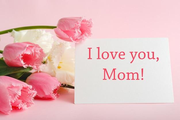 Я люблю тебя, мама текст на подарочной карте в букет цветов на розовом фоне. открытка для мамы. с днем матери. доставка цветов. открытка в цветах для женщин. открытка в розовых тюльпанах.