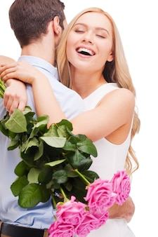 Я так сильно тебя люблю! красивая молодая влюбленная пара обнимается, пока женщина держит букет розовых роз и улыбается, и оба стоят, изолированные на белом фоне