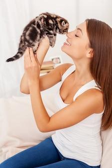 Я так сильно тебя люблю! красивая молодая женщина держит маленького котенка в руках и привязывается к нему