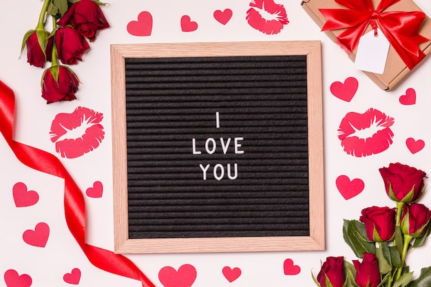 I love you - text on letter board with valentines day background - red roses, kisses and hearts.
