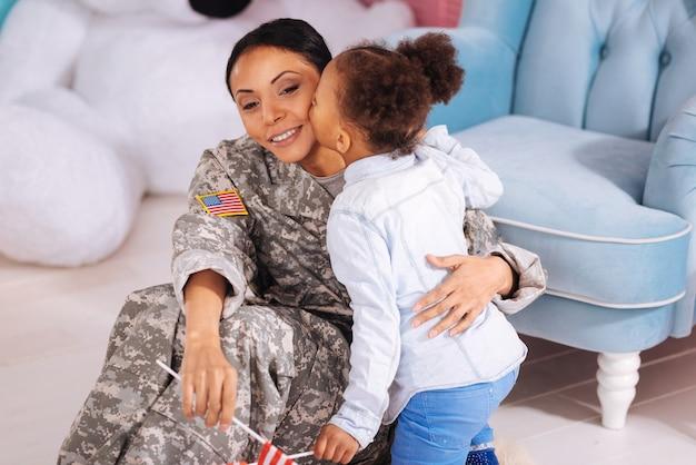 このぐらい好きだよ。彼女が彼女の隣の床に座って、彼女の手に旗を持っている間、彼女の頬で彼女のお母さんにキスするアクティブなアタッチされたゴージャスな女の子