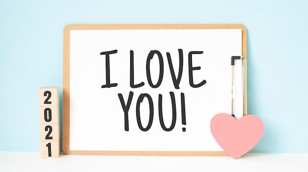 私はあなたの言葉と青い木製のテーブルの背景に赤いハートの形の装飾が施された2021キューブが大好きです。新年newyou、目標、解決策、健康、愛と幸せなバレンタインデーのコンセプト