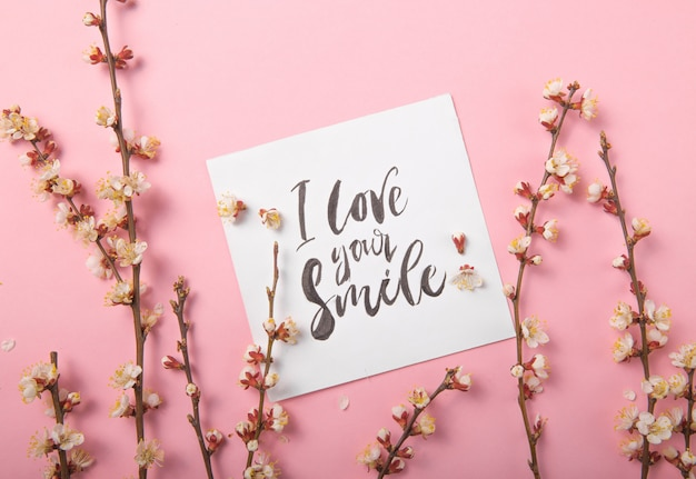 I love your smile handwritten inscription. hand drawn lettering,  calligraphy. card with spring tree brunch background, valentine, mother's day.