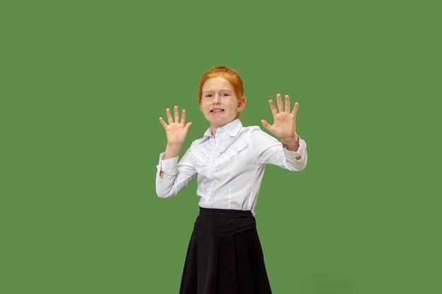 私は怖いです。怖じけ。怖い十代の少女の肖像画。彼女はトレンディなグリーンに孤立して立っています。女性の半身像