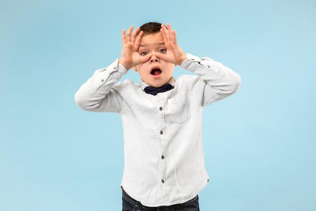 Боюсь. испуг. портрет испуганного мальчика. подросток стоя изолирован на модном синем фоне студии. мужской поясной портрет. человеческие эмоции, концепция выражения лица