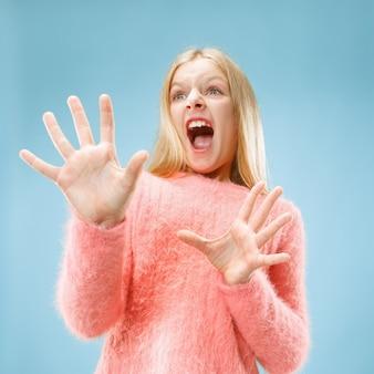 Боюсь. испуг. портрет испуганной девочки-подростка. она стояла изолированной на модном синем фоне студии. женский поясной портрет.