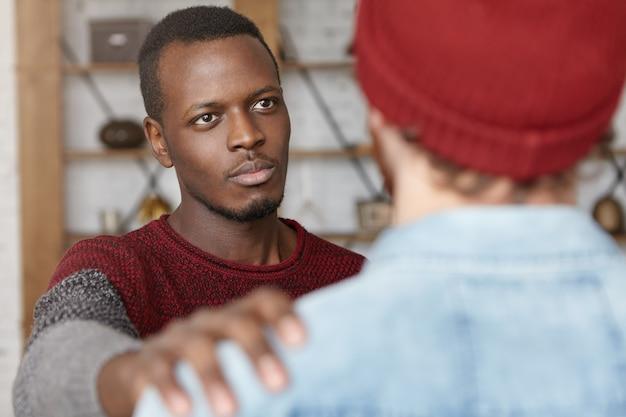 Я всегда здесь для тебя. внутренний снимок добросердечного молодого афроамериканца, сочувствующего неузнаваемому мужчине, похлопывающего его по плечу, пытаясь успокоить и успокоить своего лучшего друга