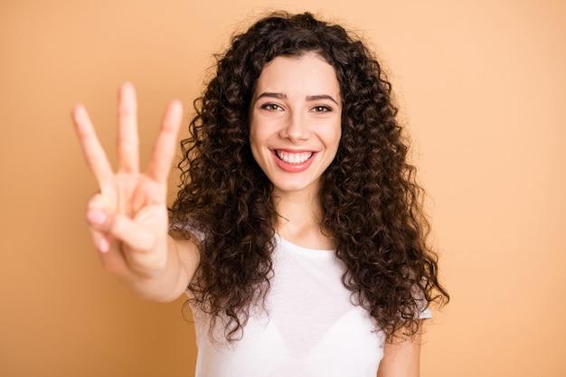 Считаю до трех! крупным планом фото смешной леди, поднимающей руку, показывающую три пальца позитивного настроения, одетую в белый повседневный костюм, изолированный бежевый пастельный цвет фона