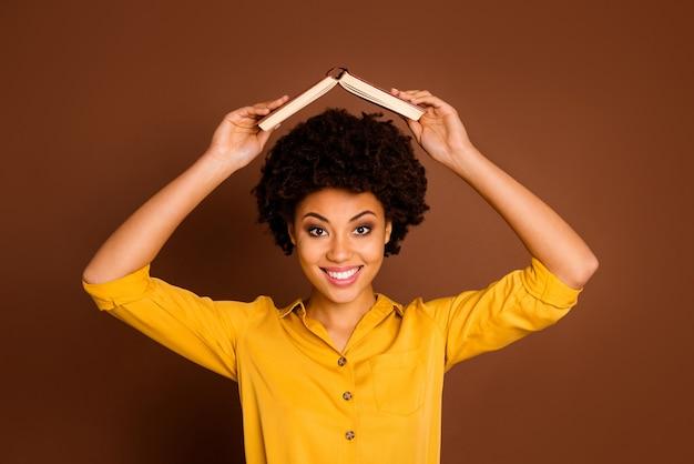 ただいま!かなり面白い暗い肌の女性のクローズアップ写真は、幼稚な気分の周りに浮気している頭の下で開いた本の宿題を保持します黄色のシャツを着て茶色の色を分離しました