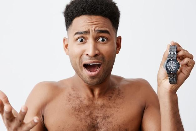 Я опаздываю на встречу. о, мой бог. плохое начало дня привлекательные красивые темнокожие африканские мужчины с вьющимися волосами расстраиваются, понимая, что он проснулся поздно и опаздывает на работу.
