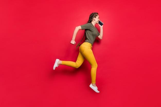 가는 중이 야! 전화 착용 캐주얼 바지 티셔츠 고립 된 붉은 색 배경을 말하는 친구와 함께 높은 실행 빠른 회의 점프 활성 아가씨의 전체 길이 사진