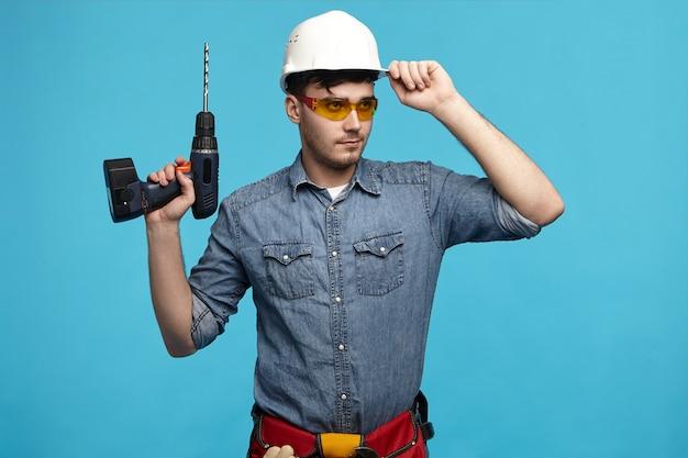 Я готов к работе. горизонтальный снимок уверенного в себе серьезного молодого небритого мужчины-работника в защитных очках, держащего дрель