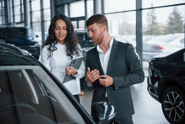 私はその新しい車にとても感銘を受けました。女性客と自動車サロンでモダンなスタイリッシュなひげを生やした実業家