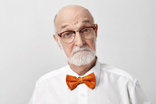 I'm very impressed. emotional unshaven european elderly retired man wearing glasses and bow tie