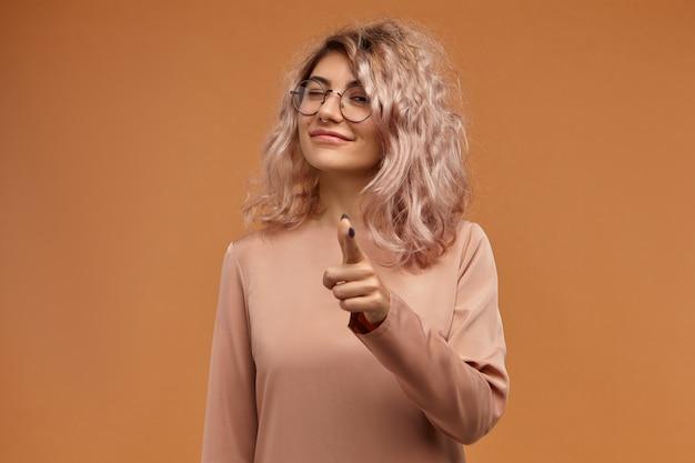 Я смотрю за тобой. горизонтальный портрет веселой игривой молодой кавказской девушки в стильных круглых очках и носовом кольце, указывая указательным пальцем на камеру и подмигивая. язык тела