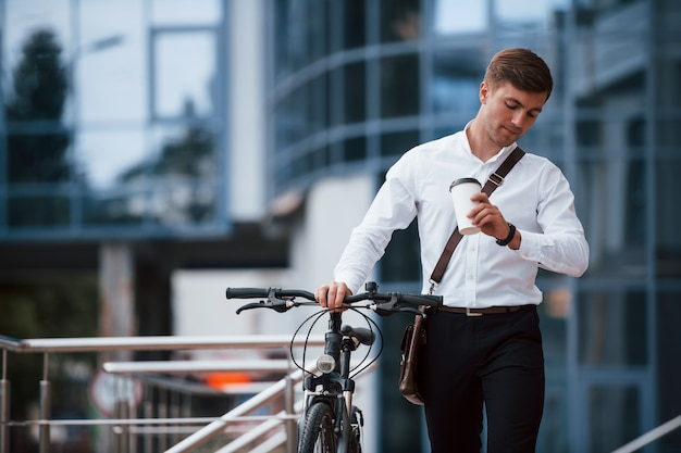I'm not will late. businessman in formal clothes with black bicycle is in the city.