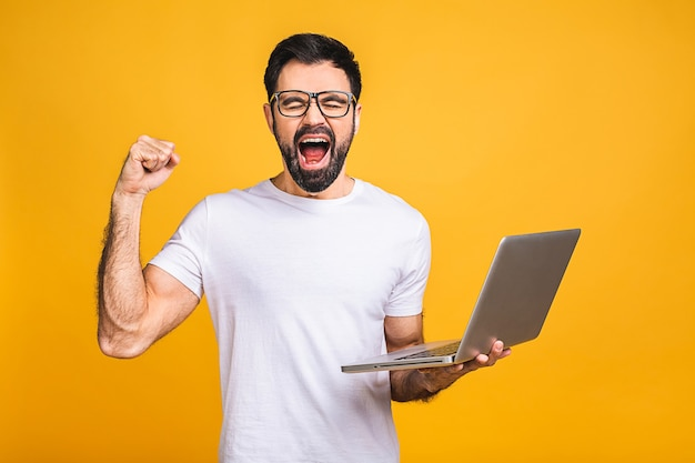 I'm a winner! happy man holding laptop and celebrating his success over yellow background.