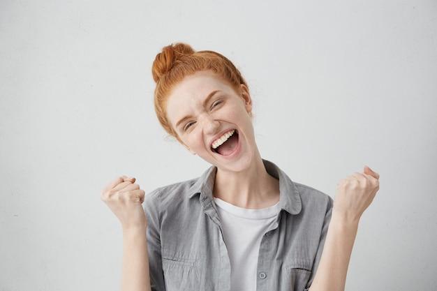 나는 그것을 만든! 행복한 흥분된 긍정적 인 젊은 여성이 주먹을 움켜 쥐고 비명을 지르며 좋은 소식, 성공 또는 승리를 기뻐합니다. 사람, 라이프 스타일, 삶의 목표, 성취 및 행복 개념