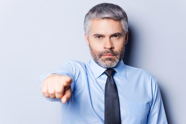 Я сделал свой выбор. уверенный зрелый мужчина в рубашке и галстуке смотрит в камеру и указывает вам, стоя на сером фоне