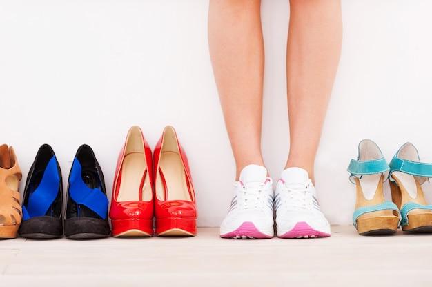 私は自分の選択をしました!高い丘の靴が彼女の近くに並んでいる間、壁に立っているスポーツシューズの女性のトリミングされた画像