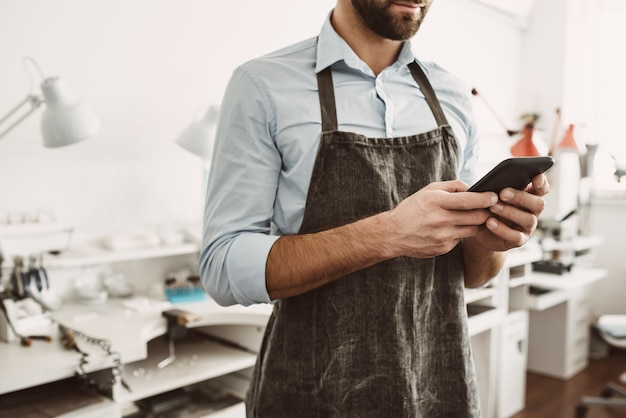 모든 과정을 온라인으로 관리합니다. 그의 보석 워크샵에 서있는 동안 스마트 폰을 들고 앞치마에 젊은 남성 보석의 초상화를 닫습니다