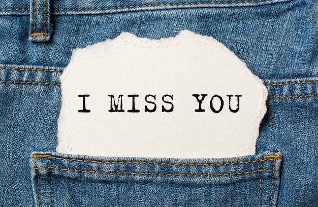 I miss you on torn paper background on jeans love and valentine concept
