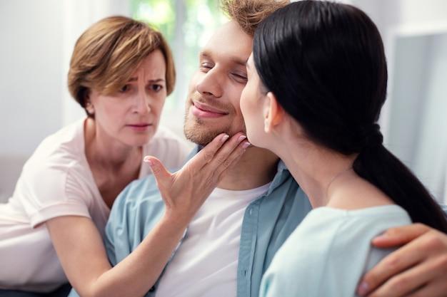Мне нужно внимание. грустная пожилая женщина трогает щеку своего сына, нуждаясь в его внимании Premium Фотографии