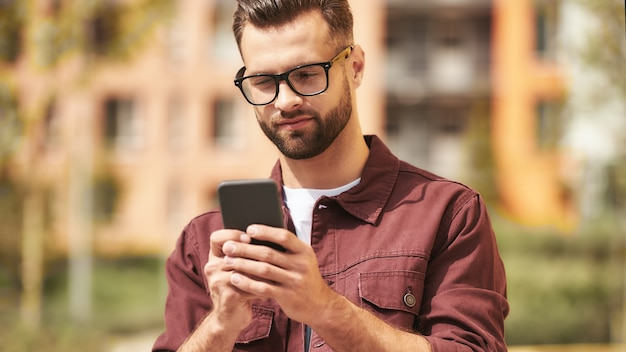 I need to call. handsome bearded man in casual wear and eyeglasses looking at his smartphone while standing on the street. lifestyle. digital. communication