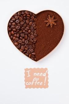 Мне нужно кофе. кофейное сердце из зерен и порошка растворимого кофе. изолированный на белой поверхности.
