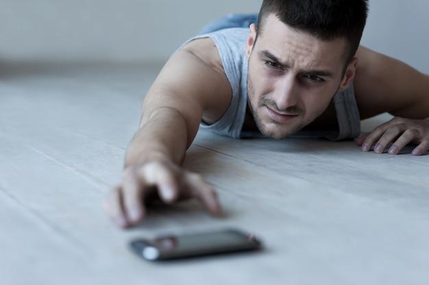도움이 필요해! 좌절된 젊은이 바닥에 누워 휴대 전화에 손을 기지개
