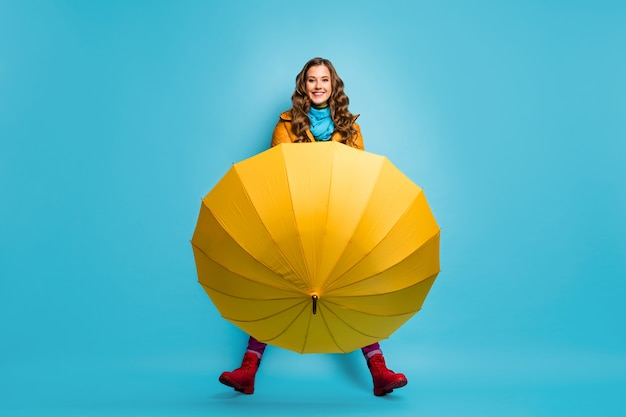 I don't need it! full length photo of pretty lady hold umbrella enjoy spring sunny day street wear yellow overcoat blue scarf trousers red boots isolated blue color wall