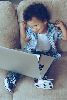 I need a little break! high angle view of little african baby boy stretching while sitting on the couch at home with laptop on his knees